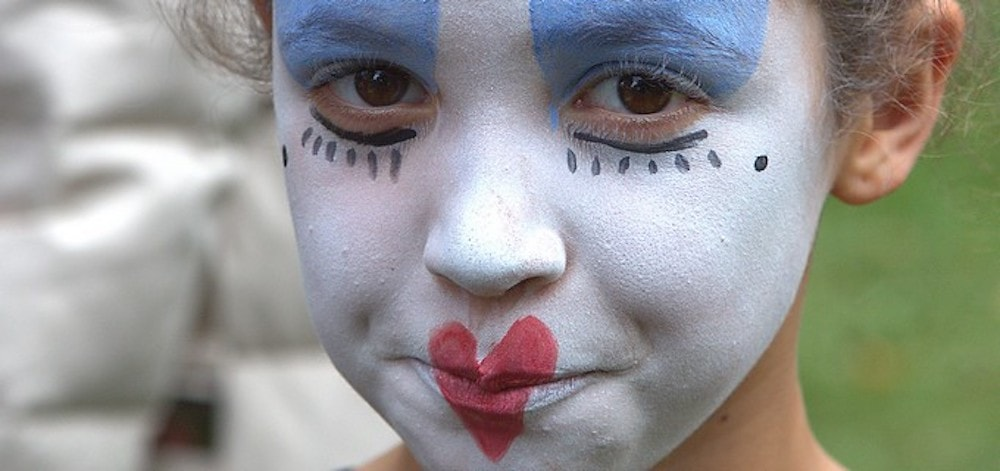 little girl with white face paint red heart lips