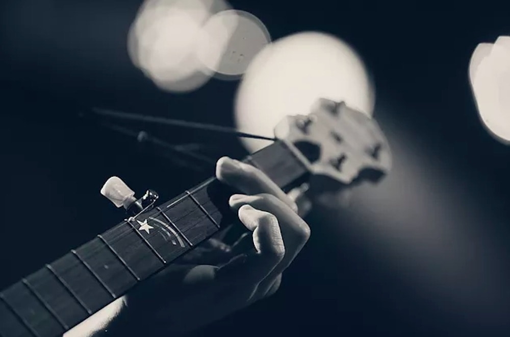 Hand on guitar string close up black and white