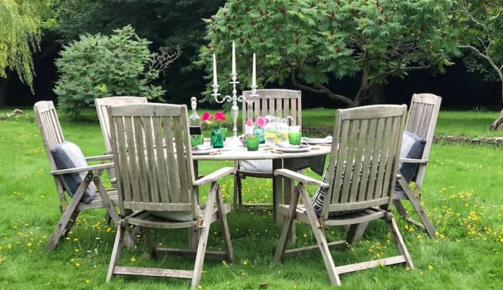 wooden garden table and chairs in green, lush garden with candelabra on table and roses in jars