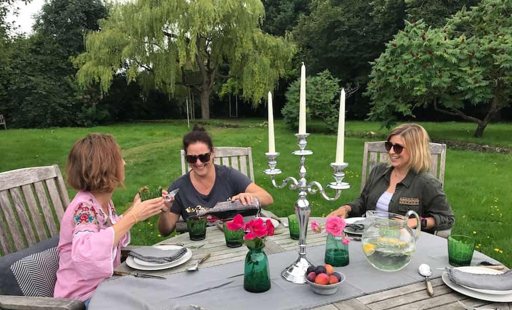 three ladies sitting in garden laughing at dining table