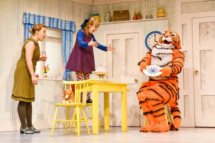 girl actress standing on yellow table holding arms open to tiger sitting on a. chair holding a plate lady in green dress with a shocked face