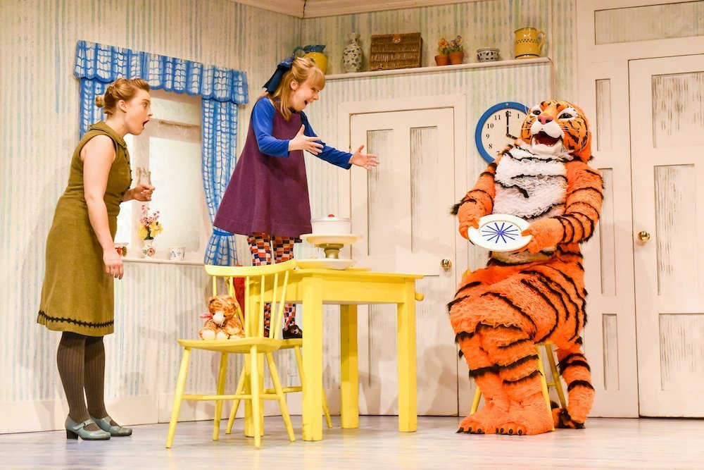 girl in purple dress standing on yellow table holding arms out to tiger sitting on chair holding a plate lady in green dress looking shocked