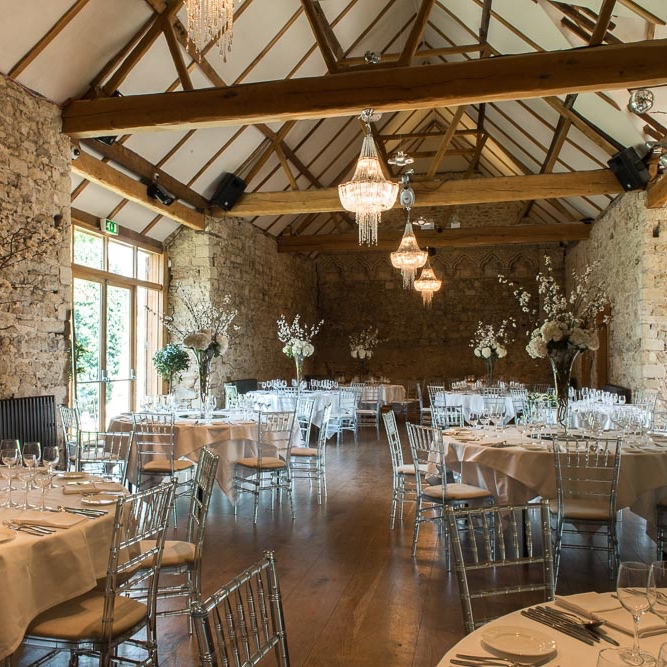 wedding reception in wood beam ceiling barn white table cloths silver chairs