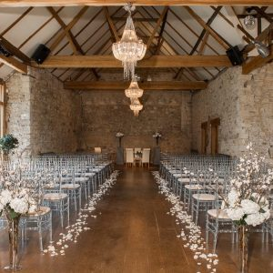 wedding ceremony in wood beam ceiling barn silver chairs lined up hanging chandeliers