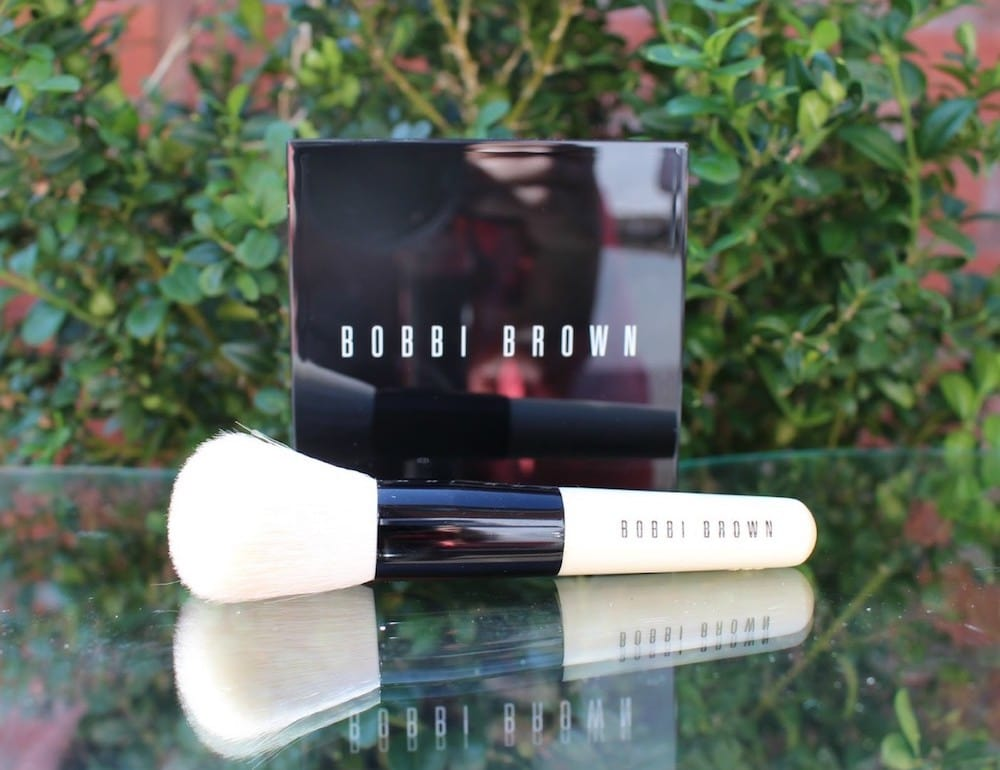 Bobbi brown black compact white brush on glass table in garden