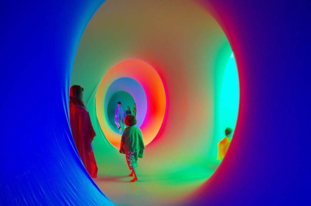 people inside brightly coloured tunnels
