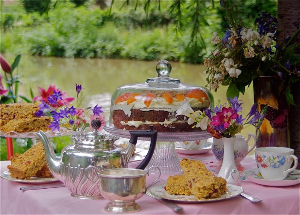 pink table clothe cake on stand flowers in vase table by river