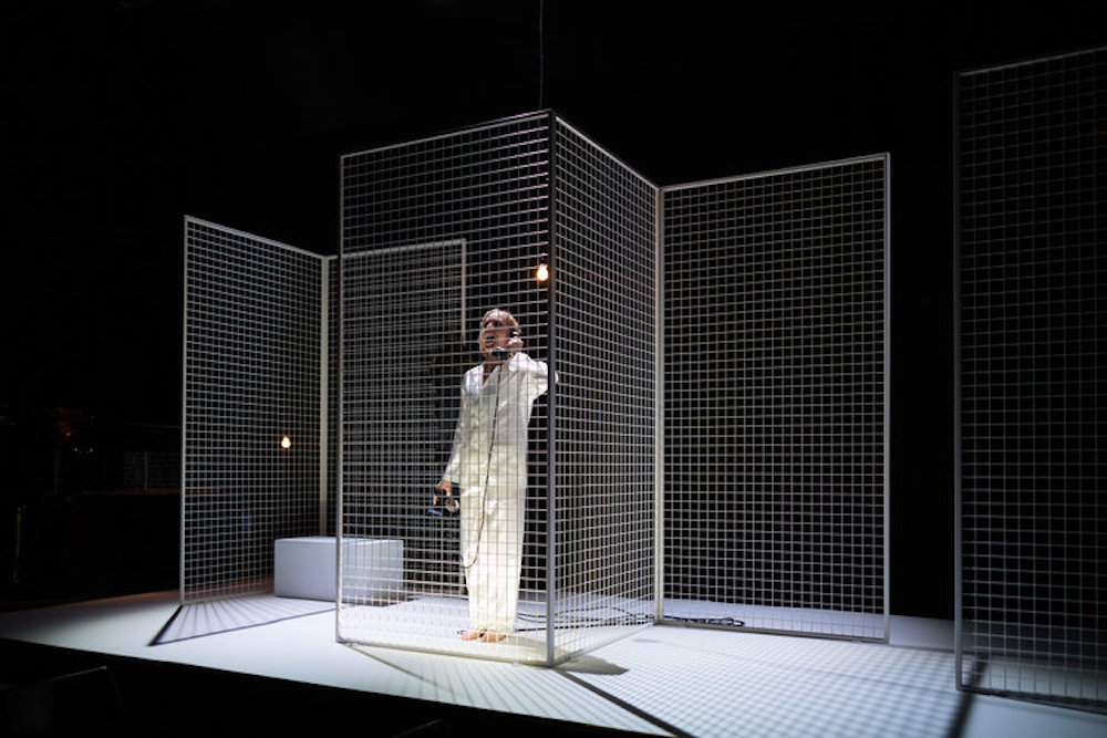 woman white suit telephone metal cage on stage