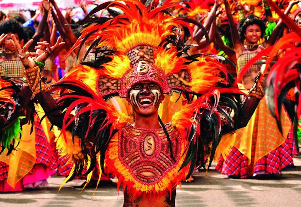 performers in bright orange costumes feather headdress smiling
