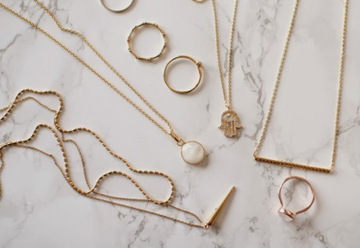 fine gold jewlerry necklaces rings on marble surface