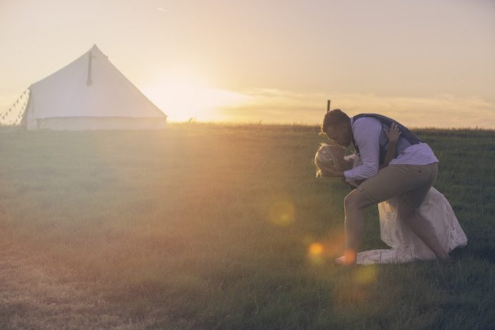 couple kissing under sunset over tent