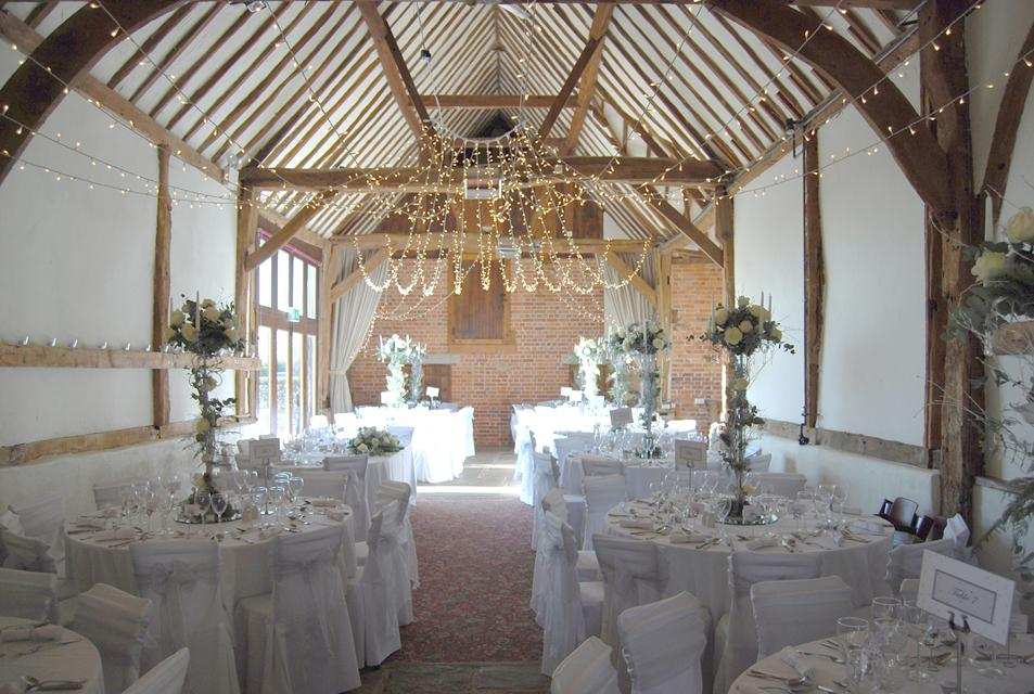 wedding reception in barn wooden beam ceiling white table clothes and chars floral centrepieces hanging fairy lights