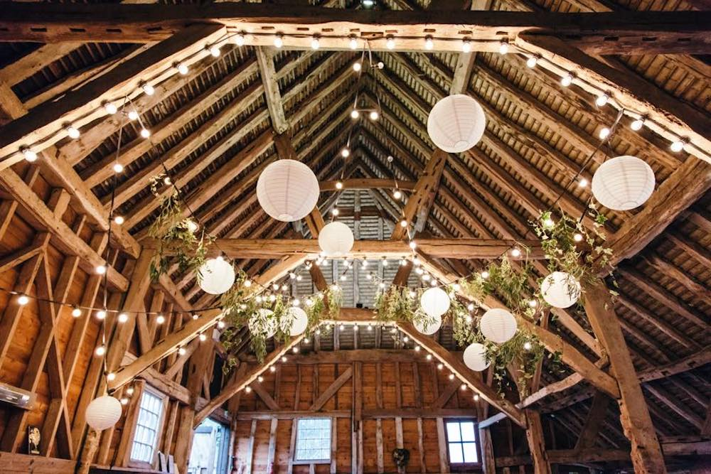 wood beamed ceiling barn fairy lights hanging and flowers wedding reception