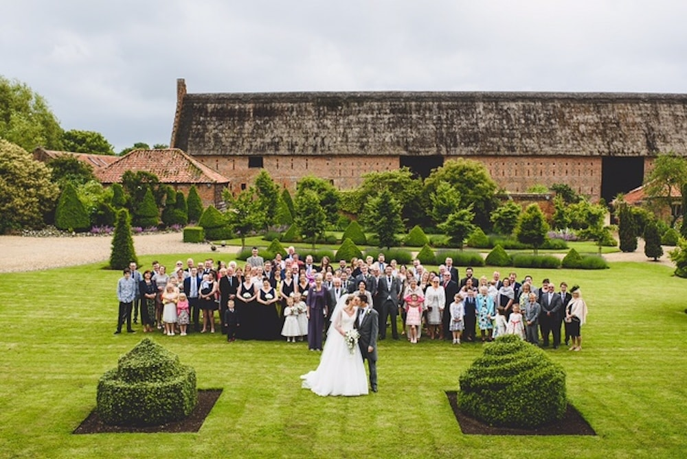 barn with wedding party on front lawn by hedges