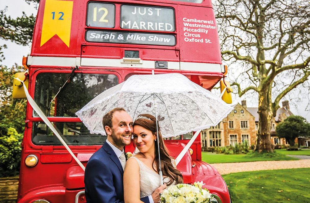 big red bus with bride and groom under umbrella smiling