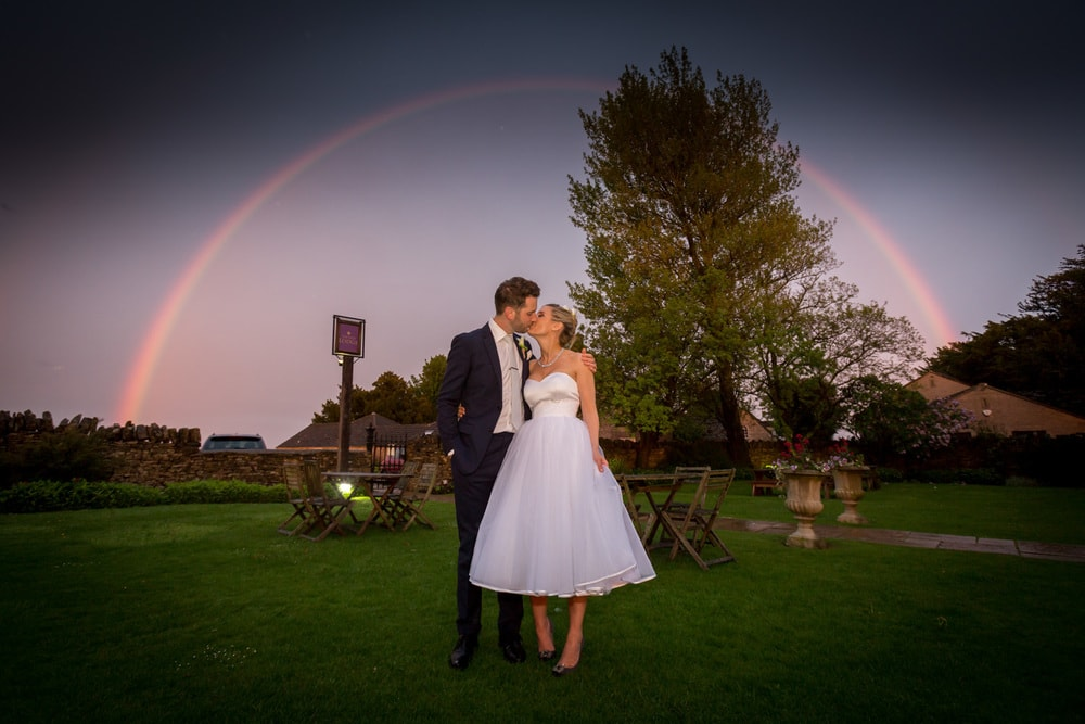 bride and groom kissing under rainbow on a field
