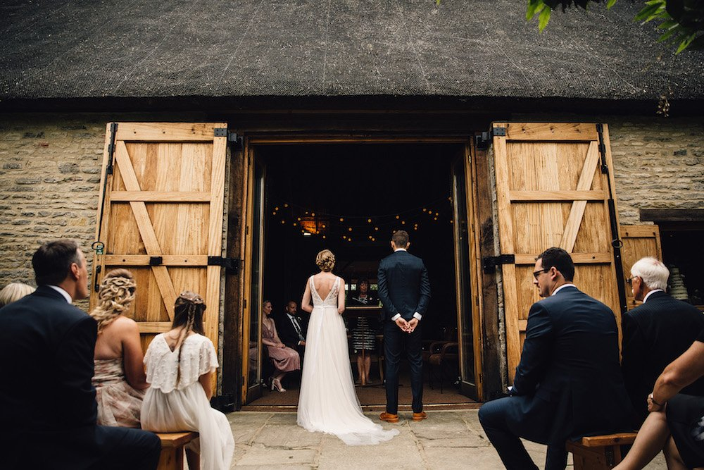 wedding ceremony outside wooden barn doors bride and groom standing side by side