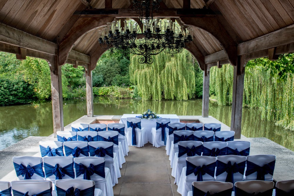 wedding ceremony on deck by river with willow trees arch wood canopy white chairs with blue bows