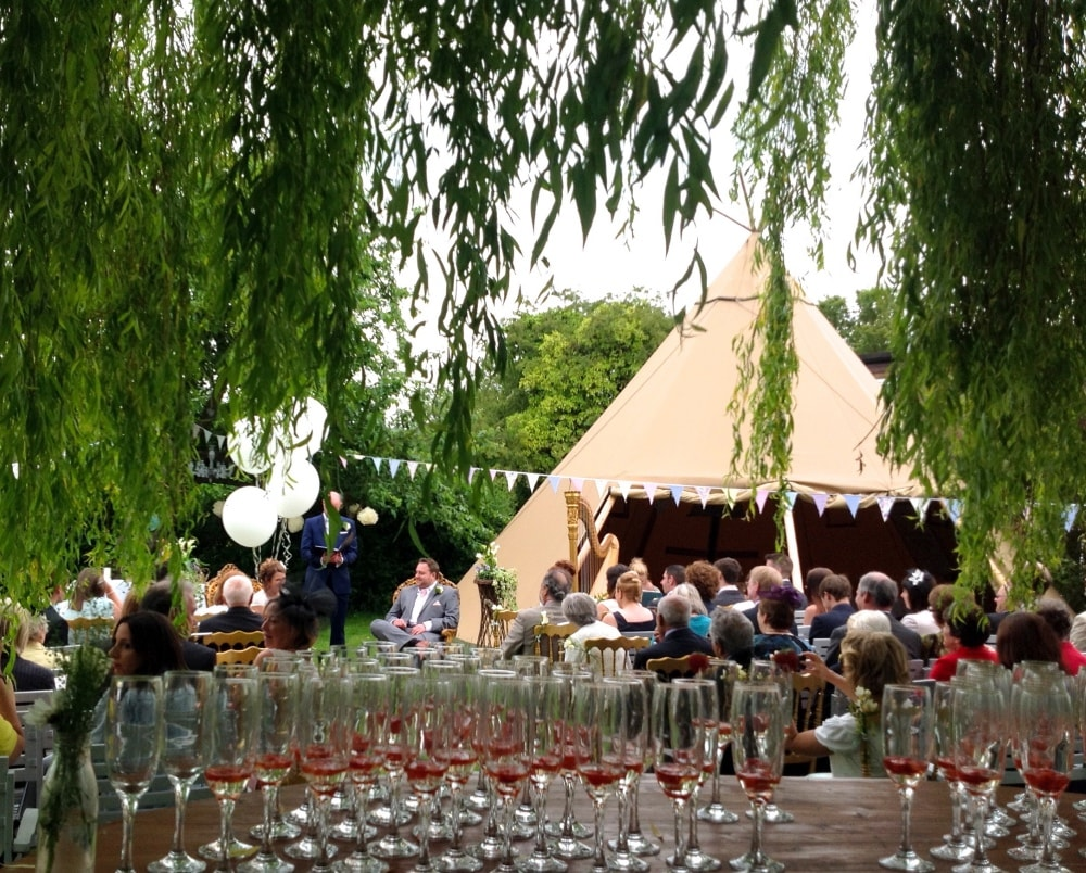 willow tree hanging over teepee and champagne glasses on table