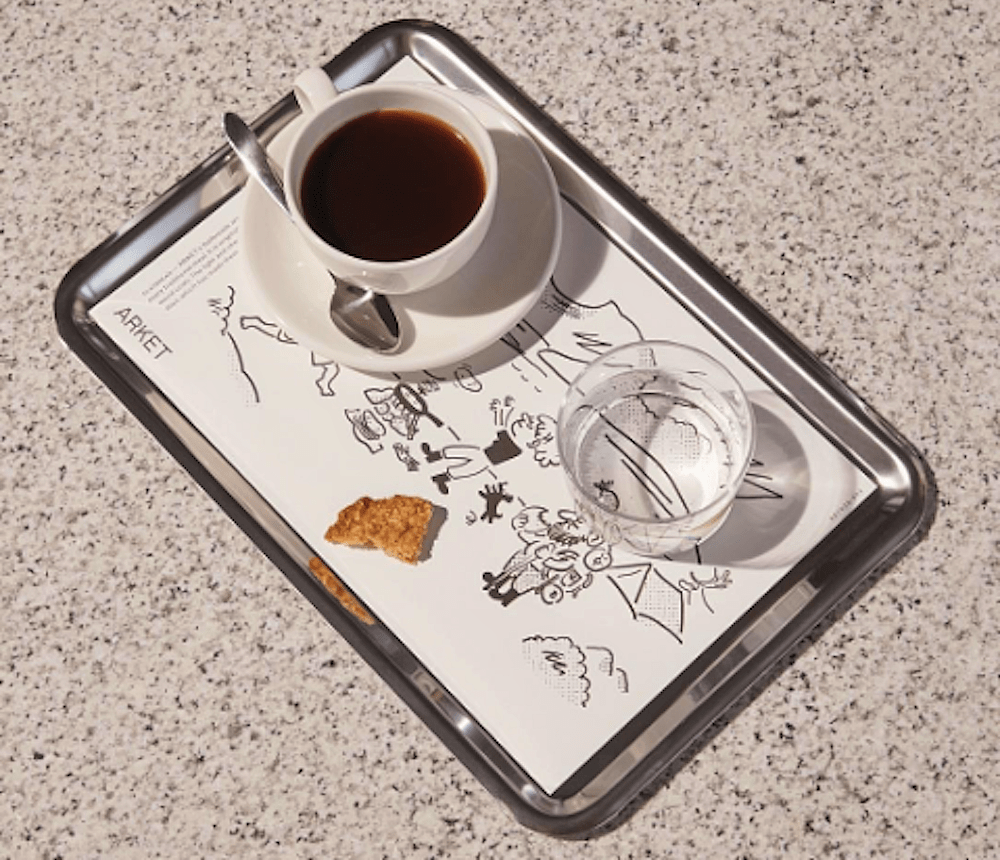 arket cafe paper place mat on silver tray white tea cup and saucer silver tea spoon half eaten biscuit and glass of water