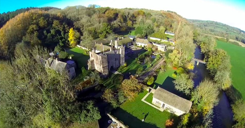 aerial view of stone castle and grounds lots of trees