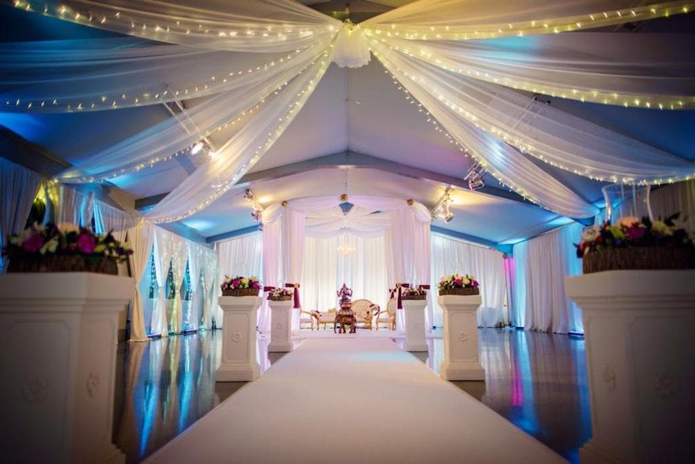 white carpet leading towards golden elephant statue white pillars with flower arrangement on top material with lights attached on ceiling