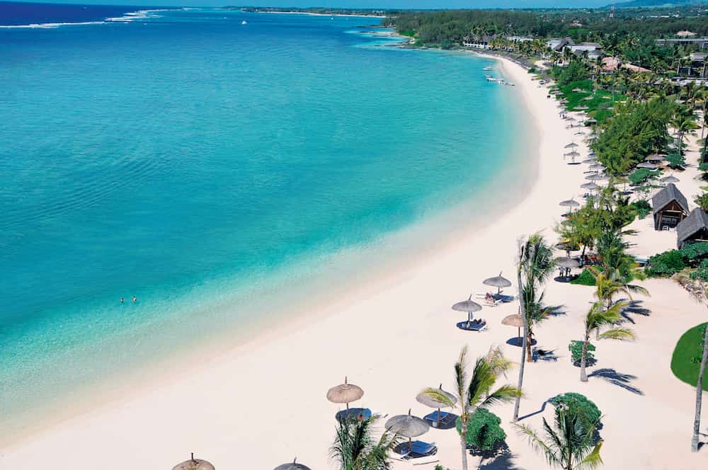 white sands and turquoise waters with lush forest and umbrellas on the beach in the Caribbean