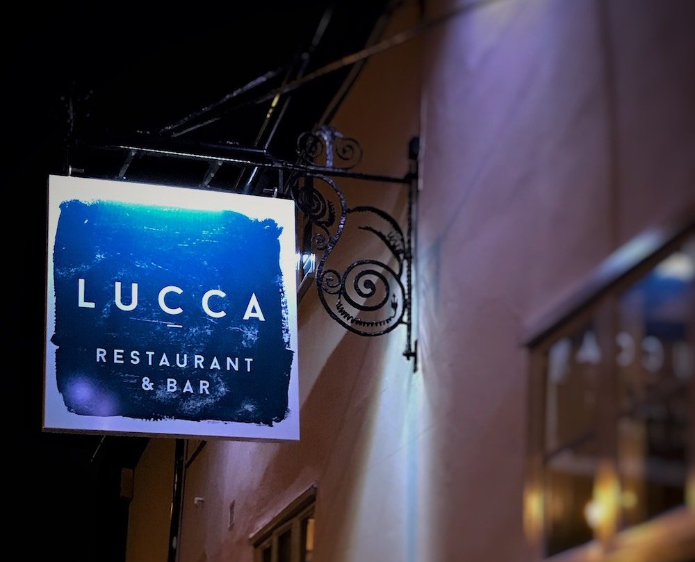 luck restaurant sign on side of wall at night