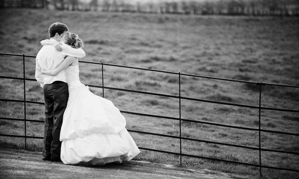black and white photo of bride in white dress hugging groom by a field and metal fence
