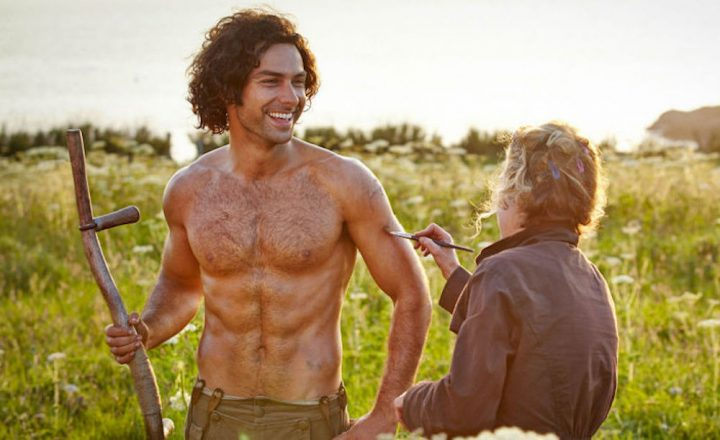 poldark actor holding stick topless in field with lady painting oil on him