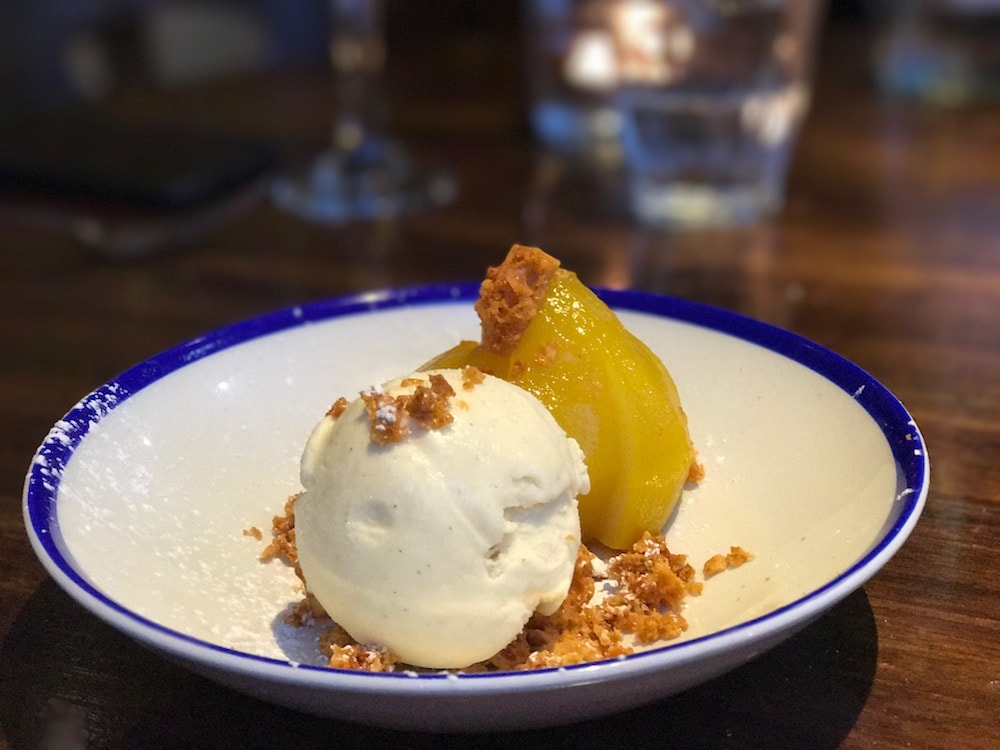poached pear vanilla ice cream and biscuit crumbs in white bowl with blue rim