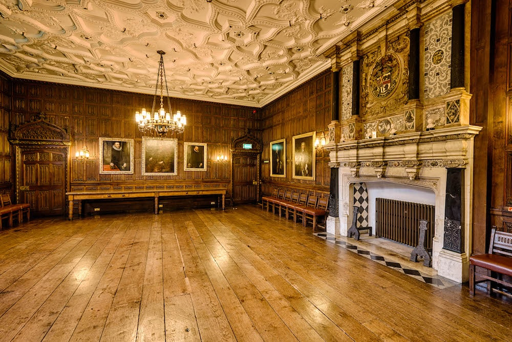 hall with grand fireplace shiny oak floor chandelier portraits on walls
