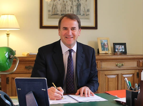 headmaster sitting at desk smiling with pen in hand