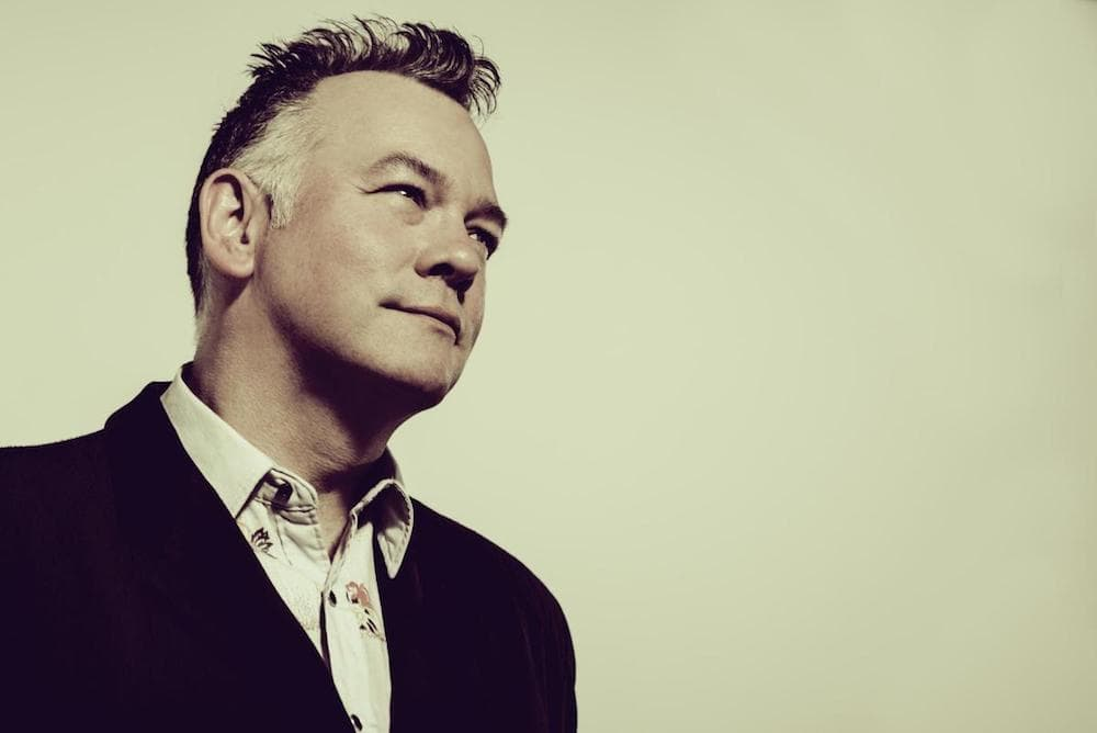 Stewart lee looking into distance wearing suit beige backgdrop