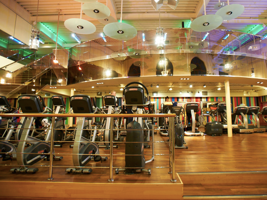 wooden floor bright gym running machines green lights on ceiling