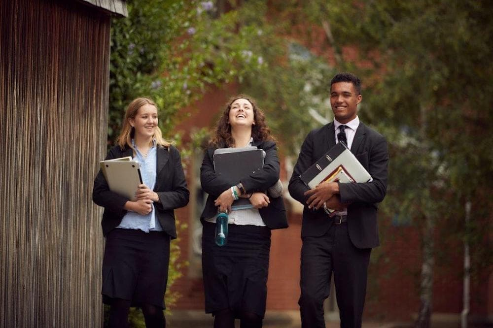 three teenage sixth formers in suits laughing holding books