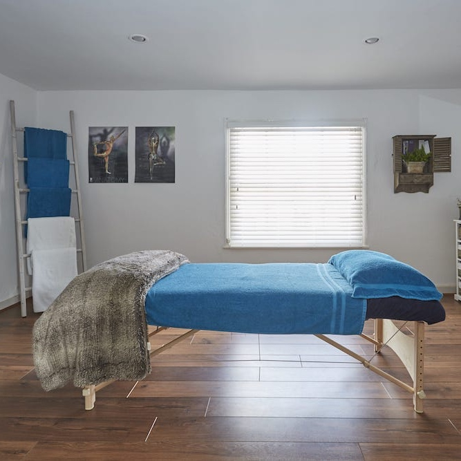 massage bed with blue sheets white walls blue towels hanging n ladder in corner