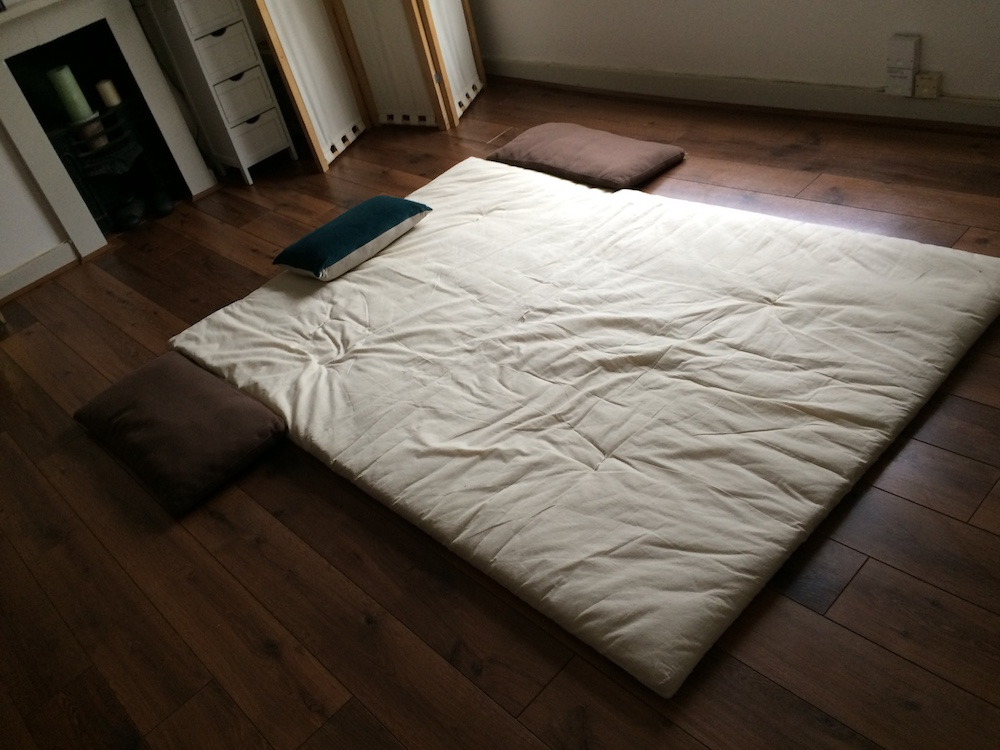 white thin matress on floor brown cushions oak wood floor