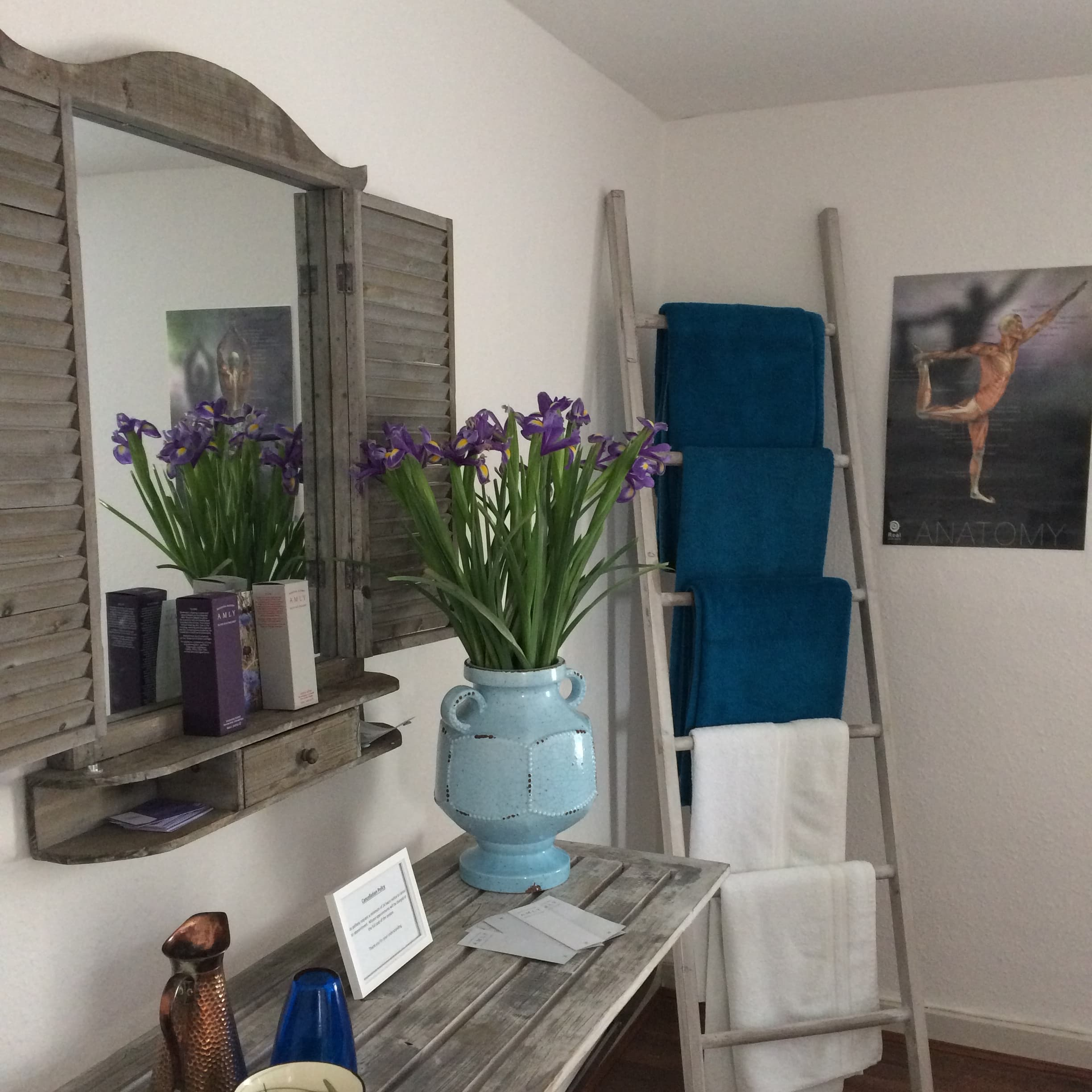 towels hanging on ladder mirror on wall with shutters shabby chic surface with blue vase purple flowers