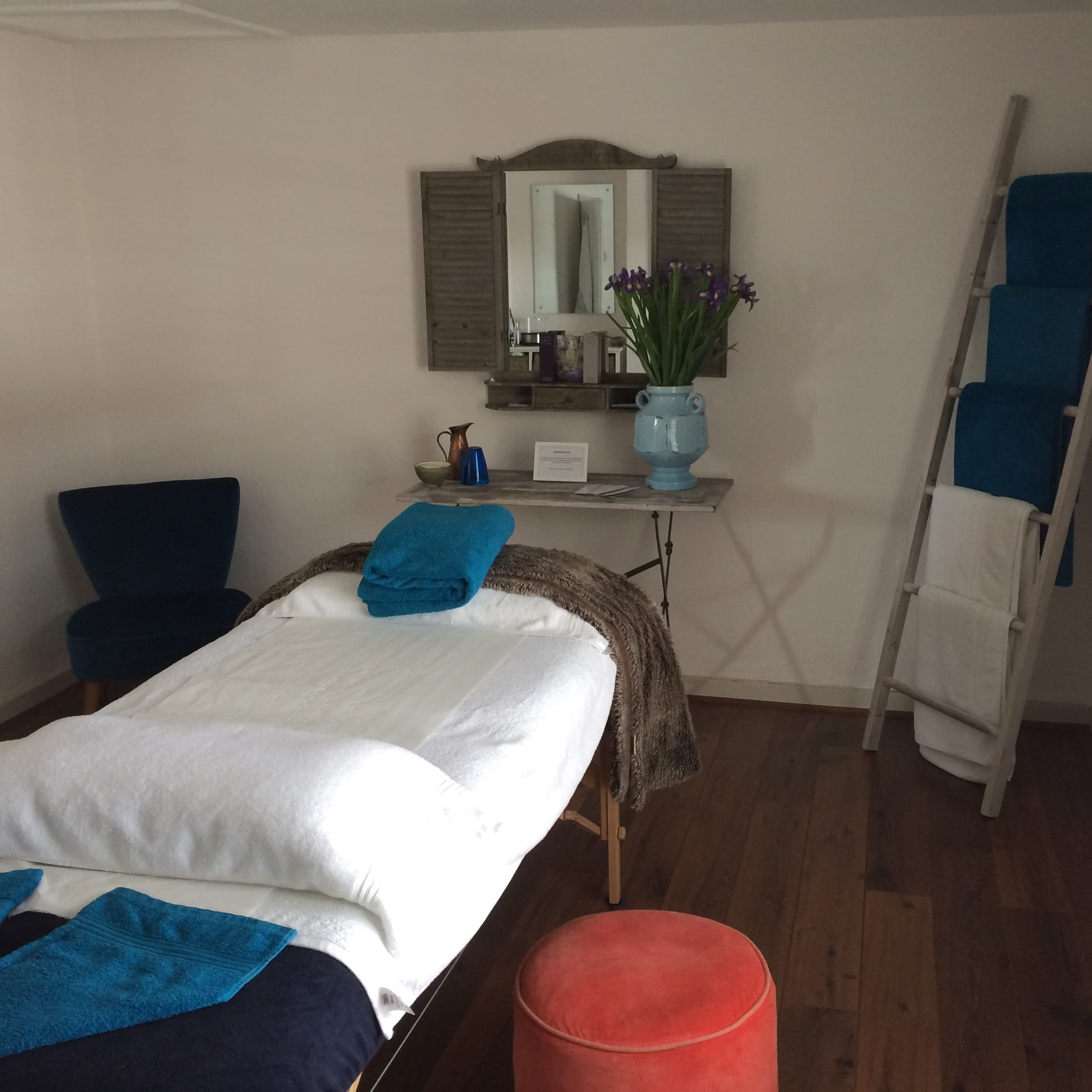 massage bed with white sheets blue towels towels hanging on ladder mirror on wall with shutters