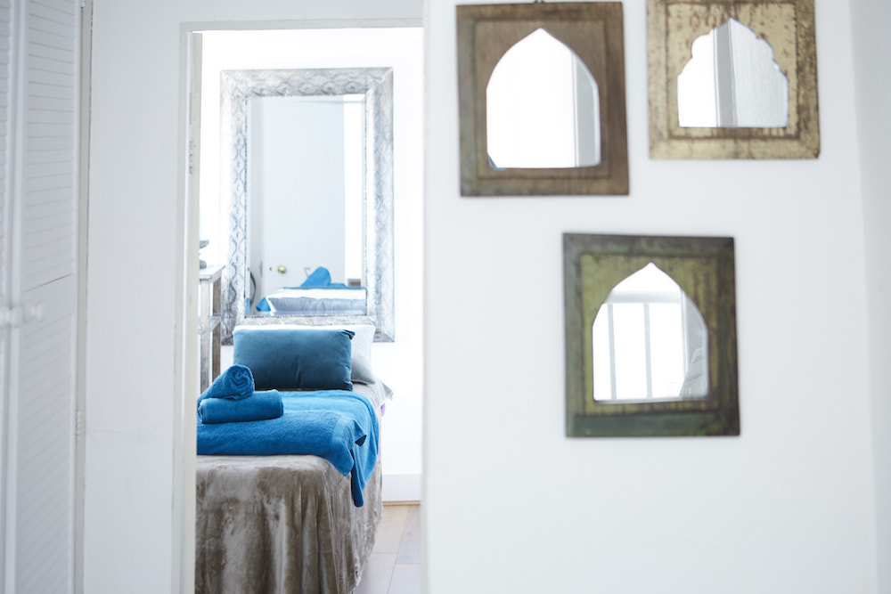 tonic massage doorway leading into room with massage bed mirrors on wall