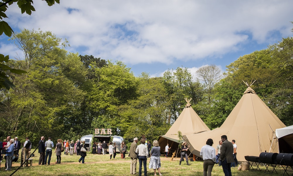 teepee in field surrounded by people and trees