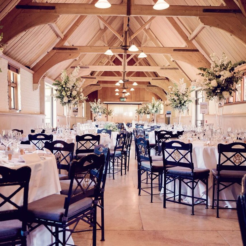 waddesdon dairy wedding reception beamed ceiling white tablecloths black wire chairs