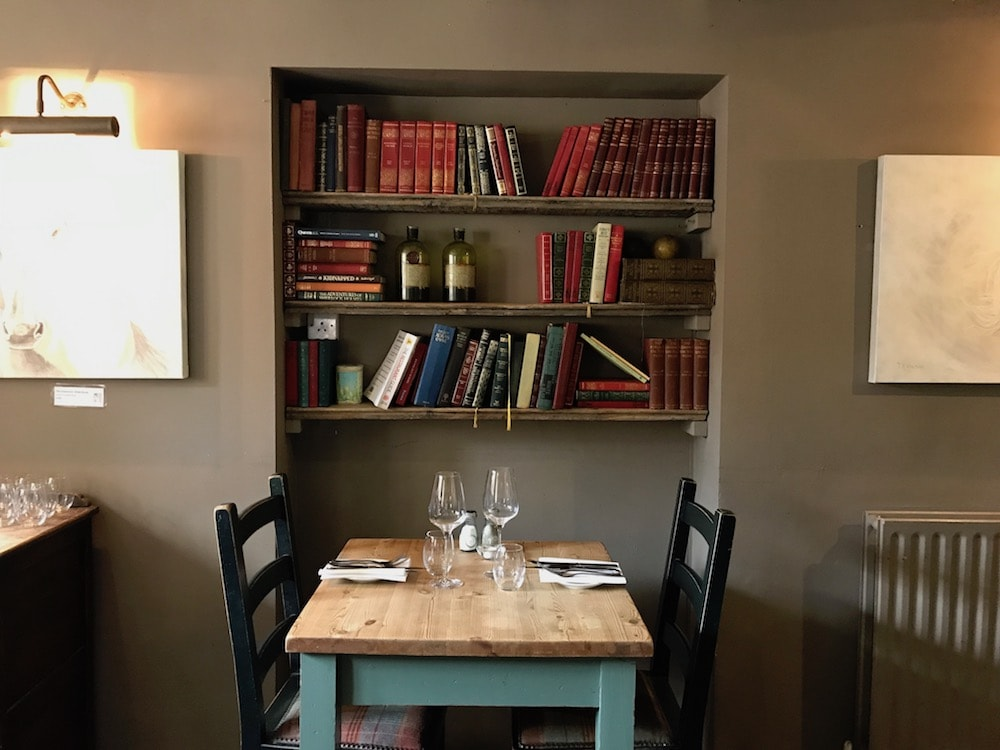 books in bookshelf above dining table and chairs beige wall
