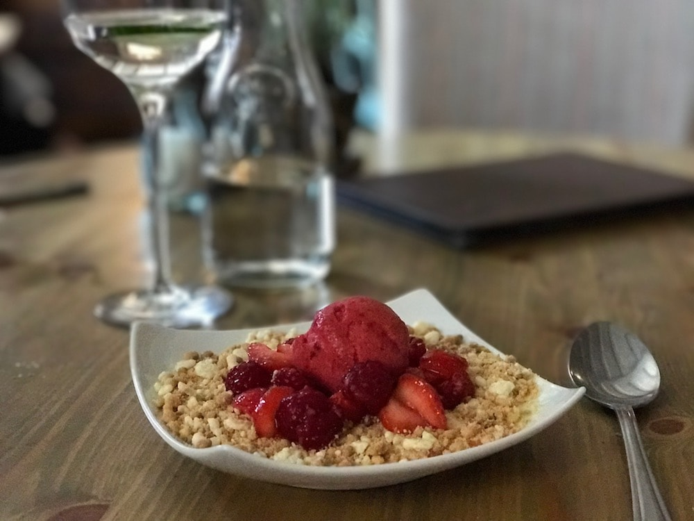 crumble topped with raspberries in square white dish silver spoon