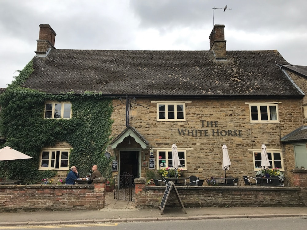 stone pub building with ivy crawling up wall slanted roof