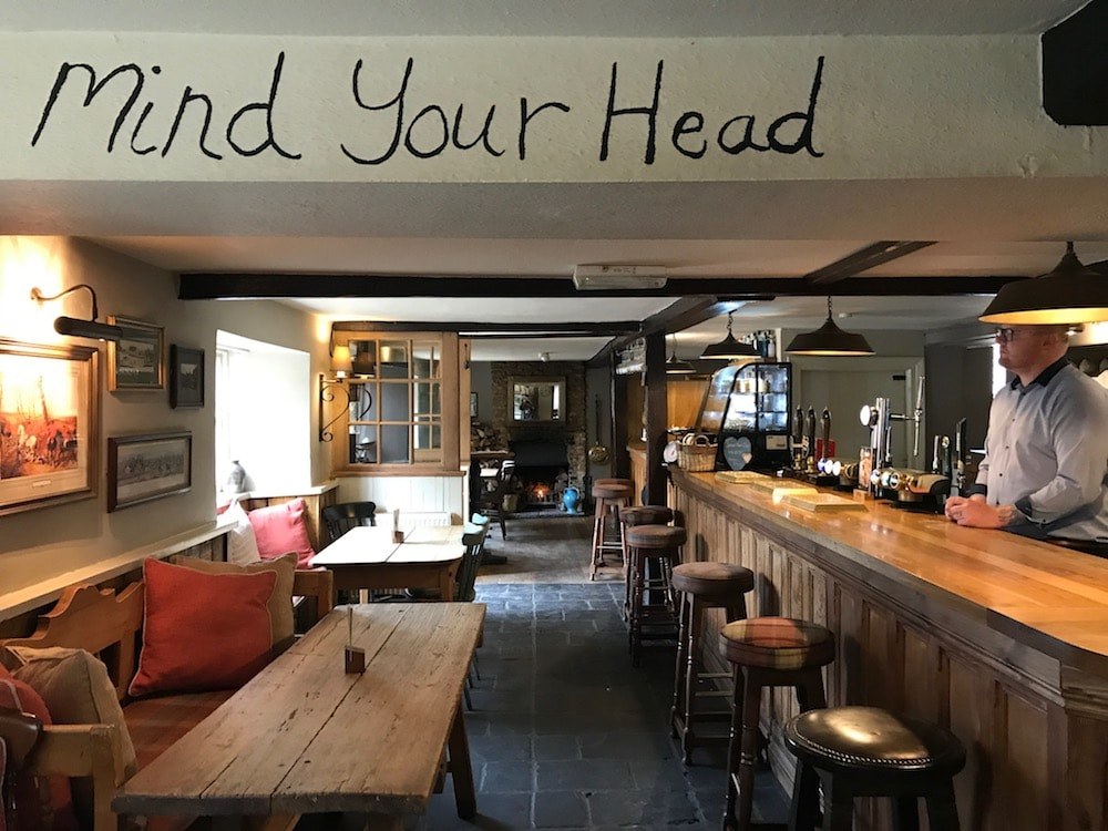 mind your head sign written on low ceiling of pub interior