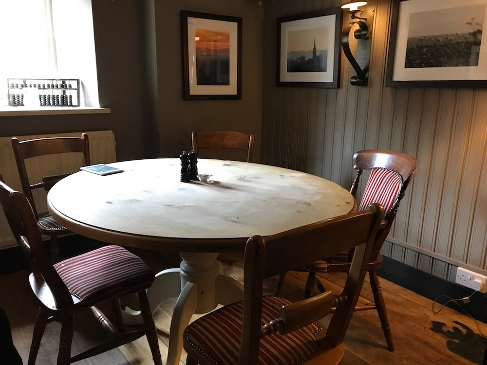 round wooden table with chairs around it