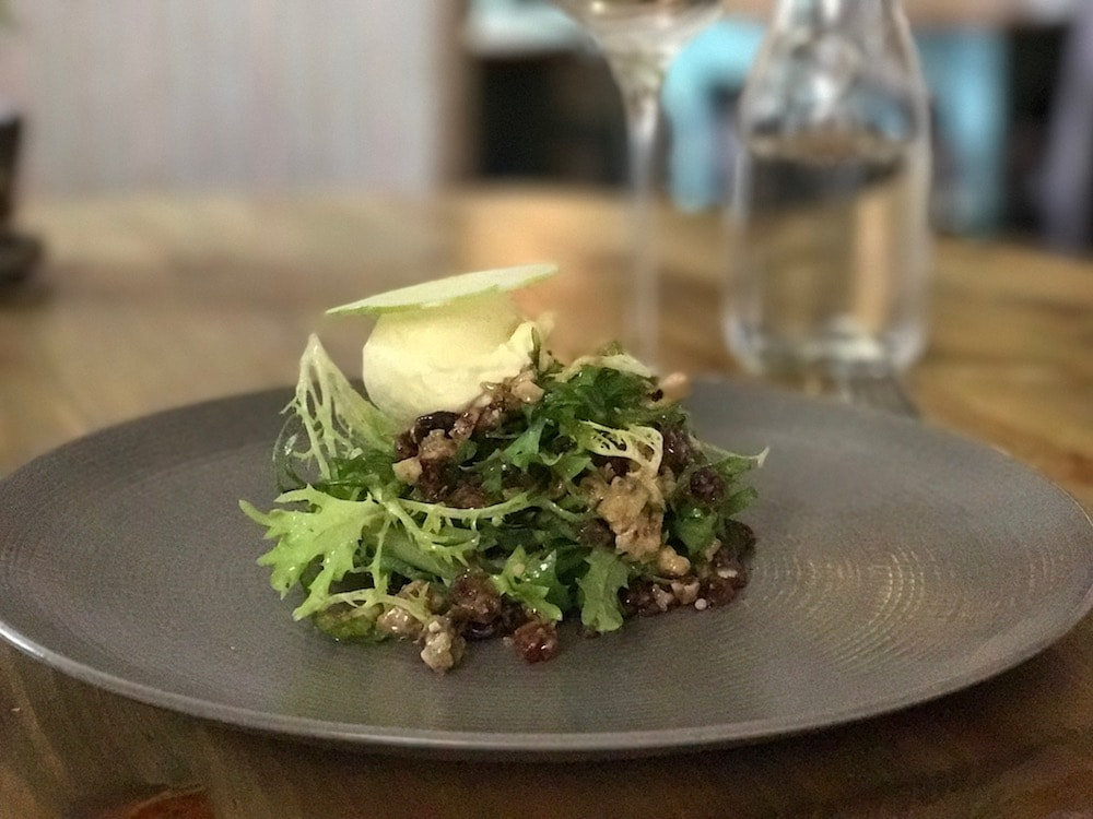 walnut and rocket salad on round grey plate