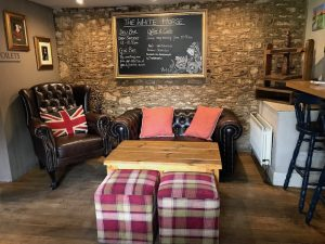 bronwn leather sofa with matching arm chai Union Jack cushion pink chequered cube stools around wooden coffee table brick wall black chalkboard hanging on wall
